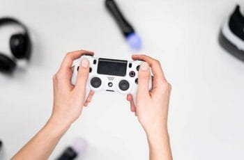 Hands holding a white PlayStation video game controller.
