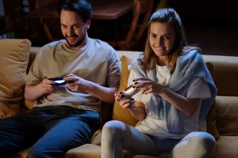 Sepasang kekasih bermain video game bersama di atas sofa.