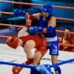 Seorang petinju merah dan petinju biru bertarung di atas ring.