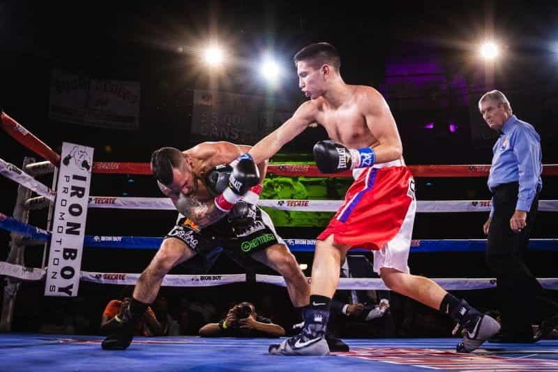 Dua petinju bertarung di atas ring, dengan penonton menonton.