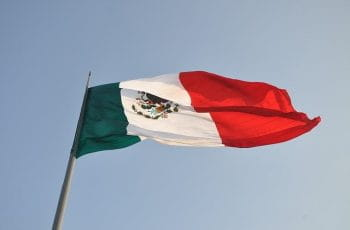 Mexico's flag flies on a flagpole.
