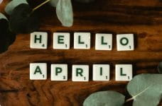 Scrabble letter tiles that say HELLO APRIL, with leaves and plants.