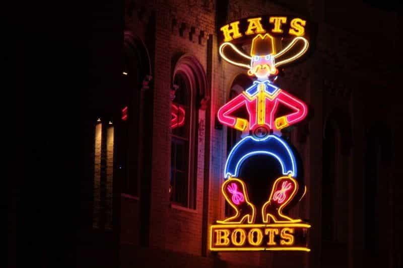 Tanda neon yang menggambarkan seorang koboi dengan kata TOPI di atas kepalanya dan kata SEPATU di bawah sepatu botnya.