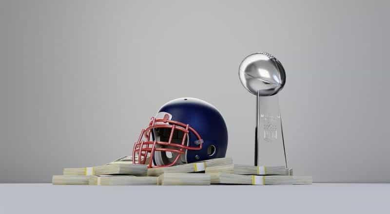 Helm sepak bola Amerika duduk di atas tumpukan uang tunai di samping piala sepak bola.