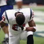 Seorang pemain NFL berseragam mengambil lutut.