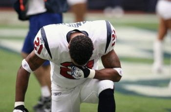 An NFL player in uniform takes a knee.