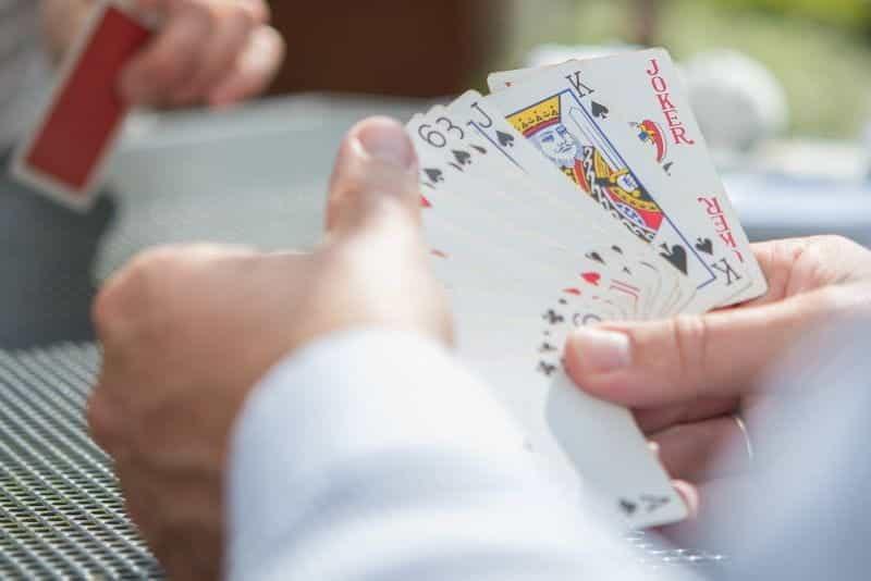 Seorang pemain poker memeriksa tangannya.