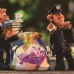 Patung-patung kecil polisi menyita barang bukti seperti uang yang dicuci dan catatan keuangan.