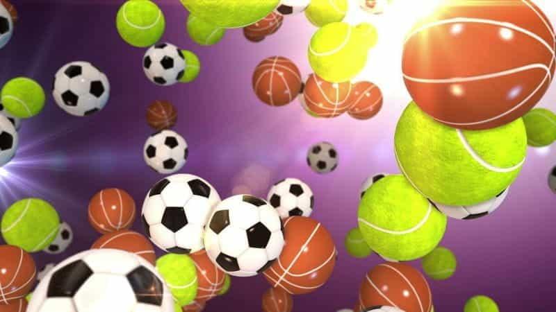 Bola tenis, bola basket, dan bola sepak melayang di depan latar belakang ungu.