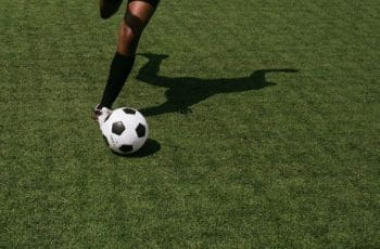 A footballer kicking a soccer ball.
