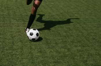 A footballer kicking a soccer ball.