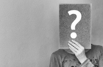 A person holding a rectangular form in front of their face with a large question mark on it.