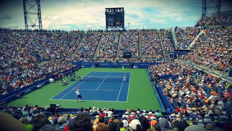 Pertandingan tenis selama turnamen AS Terbuka di stadion yang ramai.