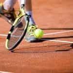 Seorang pemain tenis menggiring bola dengan raket tepat di samping kakinya.