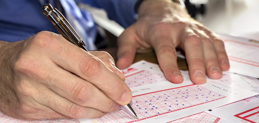 A man filling out a lottery ticket.