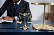 A judge or lawyer working at a desk, with scales of justice.