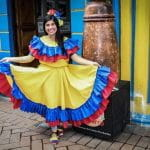 A woman wearing traditional Colombian dress holds out her skirt and smiles.