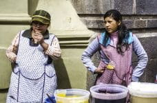 Two women street vendors sell their wares outside in Peru.