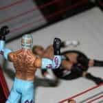 Patung-patung dari dua pejuang WWE berhadapan di atas ring.