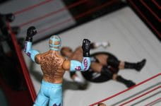 Figurines of two WWE fighters face off in the ring.