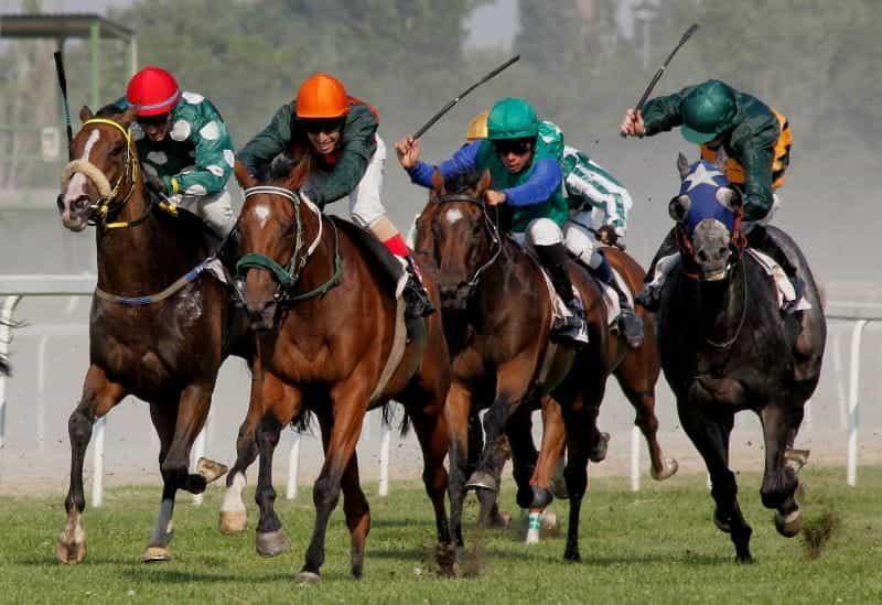 Joki dengan pakaian warna-warni berlomba dengan kuda di trek.