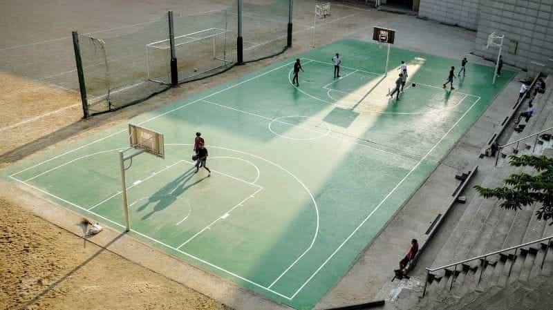 Sekelompok kecil pria bermain bola basket di lapangan luar ruangan.