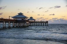 The beach during sunset with a pier jutting out into the water.