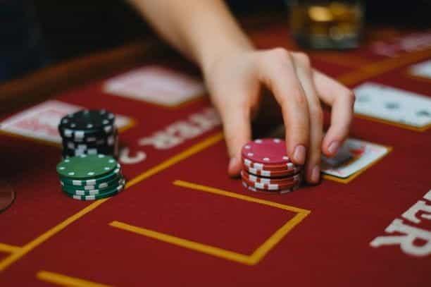 Seorang dealer memegang chip poker, dengan kartu remi.