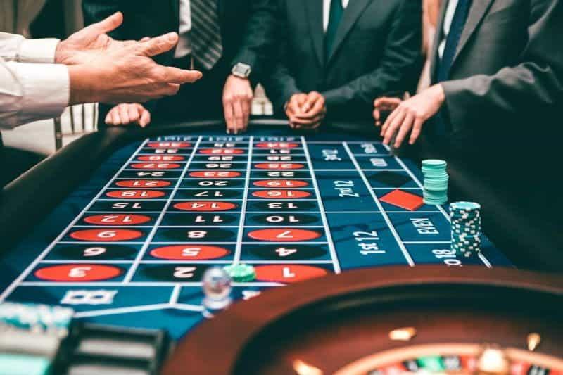 Pria berjas bermain roulette dengan chip di kasino.