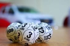 Three white numbered bingo balls on a wooden table.
