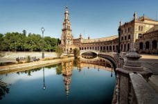 An old building curves around a canal in Sevilla, Spain.