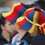 Dua wanita mengenakan topi perayaan yang diwarnai seperti bendera Kolombia untuk hari libur nasional.
