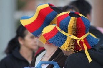 Two women wear celebratory hats colored like the Colombian flag for a national holiday.