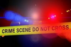 A yellow tape displaying the words crime scene do not cross in front of blue and red flashing lights.