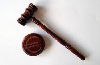 A gavel and base, with a Euro symbol featured on the gavel.