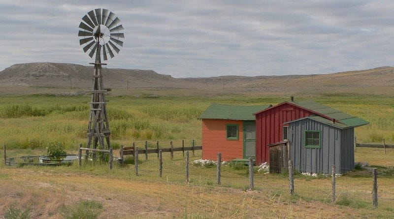Dataran tandus Nebraska, menampilkan beberapa gubuk kecil dan kincir angin.