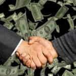 Jabat tangan terjadi dengan latar belakang terbitan uang dolar AS.