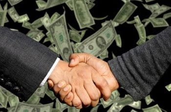 A handshake taking place on a background of flying US Dollar bills.