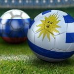 A soccer ball with the Uruguayan flag on it rests on a soccer field in front of a second soccer ball with the Russian flag on it.