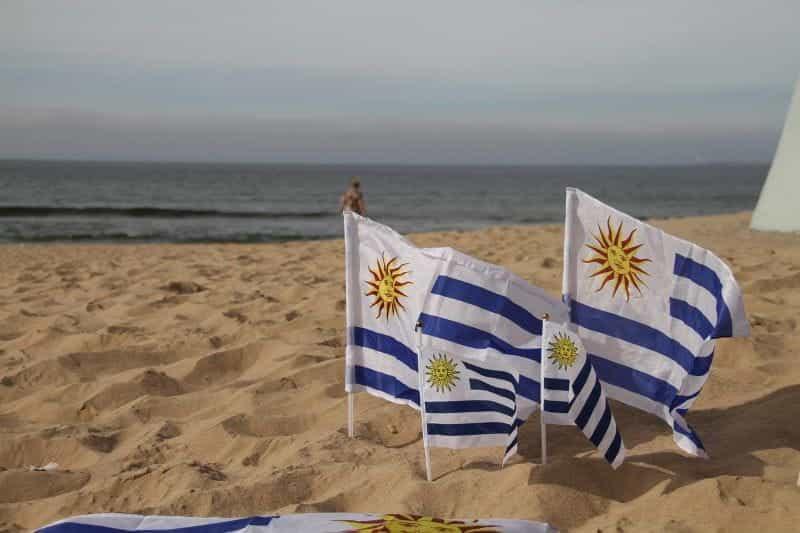 Empat bendera Uruguay dengan ukuran berbeda di pasir di pantai.