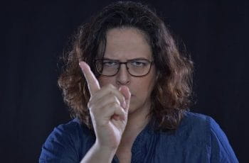 A stern-looking woman wagging her finger in a sign of warning.