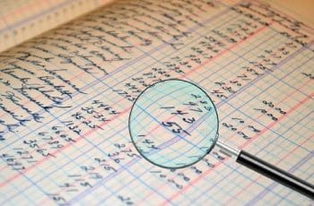 A magnifying glass zooming in on a table of numbers as part of an audit.
