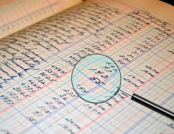Kaca pembesar yang memperbesar tabel angka sebagai bagian dari audit.