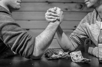 Two men arm wrestling one another on a table with US dollar bills and a beer bottle on it.