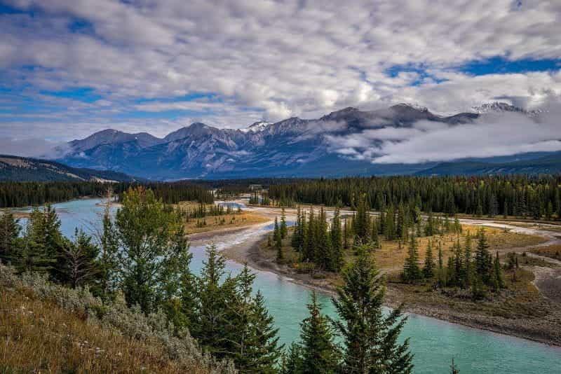 Lanskap pedesaan di Kanada, menampilkan hutan dan pegunungan yang jauh.