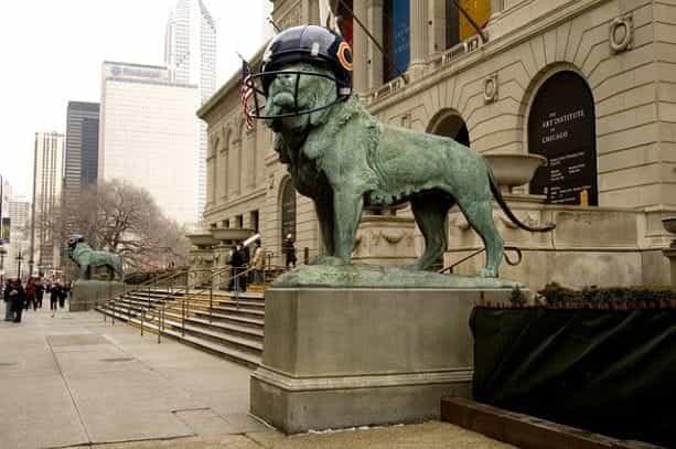 Patung singa di depan Institut Seni Chicago dengan helm Chicago Bears di atasnya.