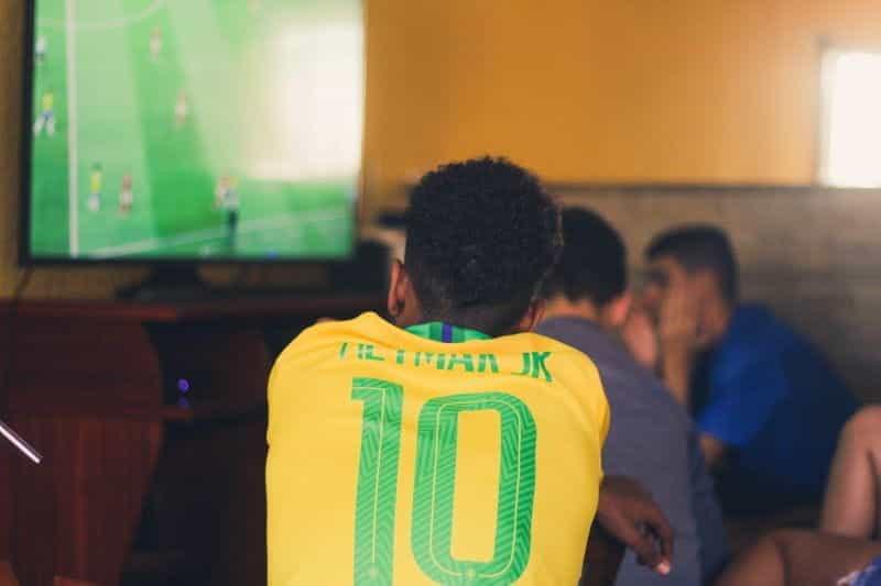 Pemuda yang mengenakan kemeja tim nasional Brasil dengan nama Neymar di atasnya menonton pertandingan sepak bola di TV.