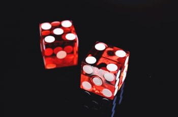 Two red dice with white spots on a black background.
