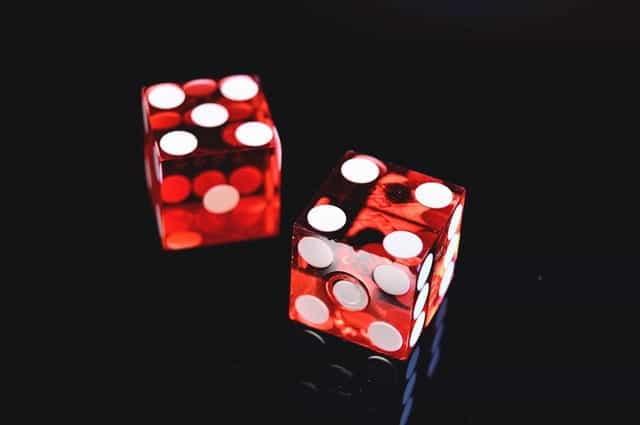 Dua dadu merah dengan bintik-bintik putih pada latar belakang hitam.