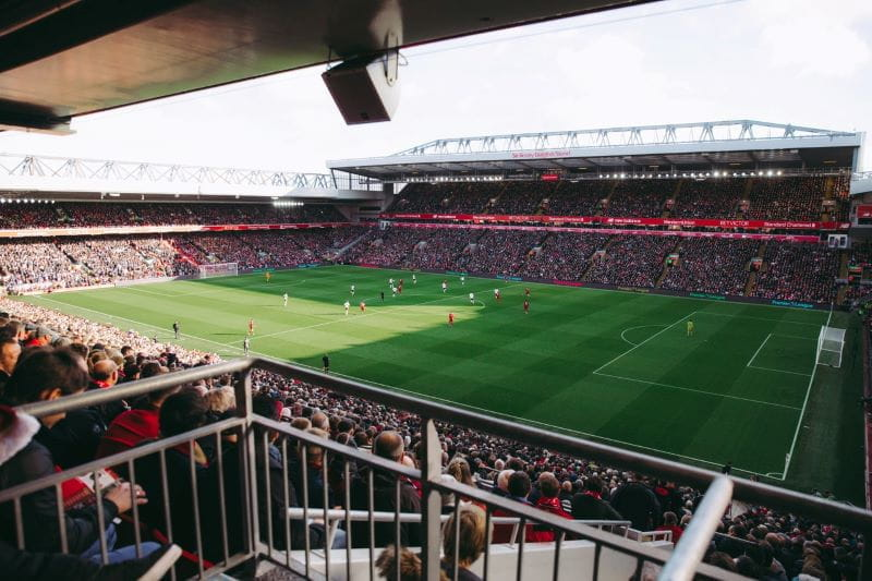 Kerumunan penggemar di stadion menonton pertandingan sepak bola.